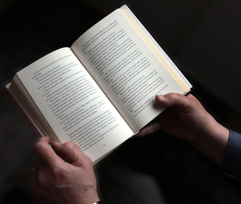 male hands holding an open book